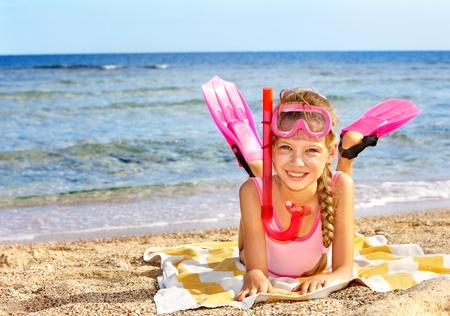 scuba goggles: Little girl  playing on  beach.