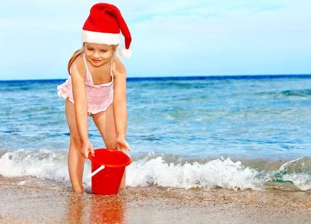 산타 모자: 해변에서 재생하는 산타 모자에있는 아이. 여름 새 해입니다. 스톡 사진