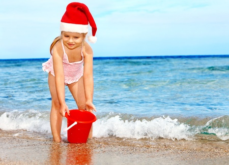 bucket and spade: Child in santa hat playing on  beach. Summer New Year.