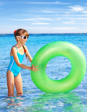 float tube: Children holding inflatable ring in sea. Stock Photo
