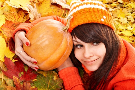 Happy young woman with  pumpkin on autumn leaves. Outdoor. photo