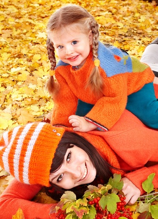 Happy family with child on autumn orangeleaves. Outdoor. photo