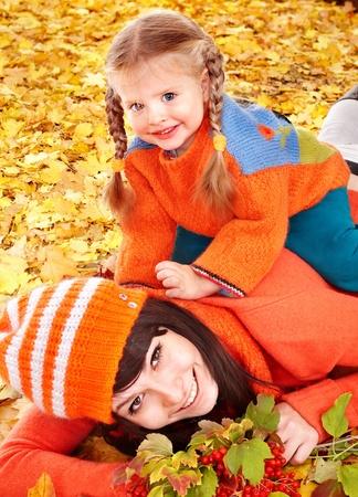 Happy family with child on autumn orangeleaves. Outdoor. Stock Photo - 10853049
