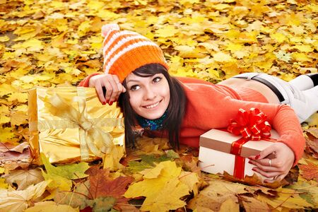 Girl in autumn outdoor holding gift box. Holiday. photo