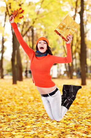 Girl with autumn leaf jump outdoor in park. photo