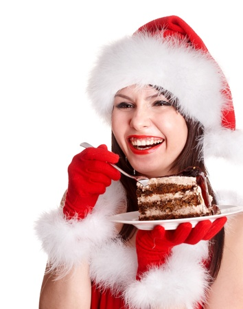 Christmas girl in red santa hat eating cake on plate. Isolated. Stock Photo - 10852836