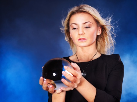Mujer hermosa joven con la bola de cristal.