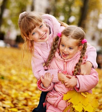 Children in autumn orange leaves. Outdoor.