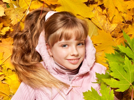 Child in autumn orange leaves. Outdoor. photo