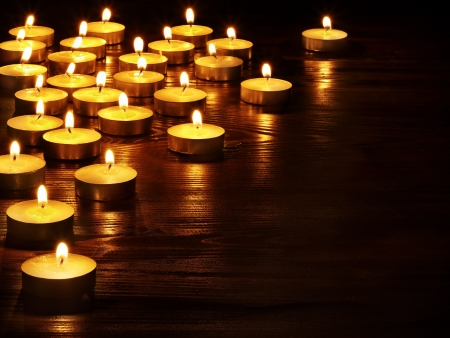 holiday lighting: Group of burning candles on  black background.