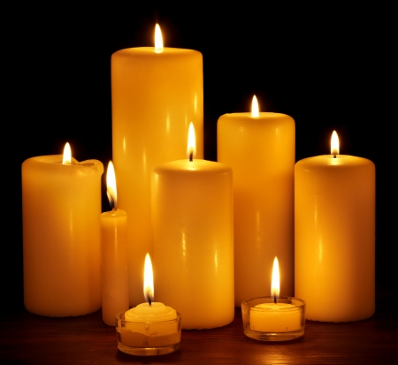 Group of burning candles on  black background.