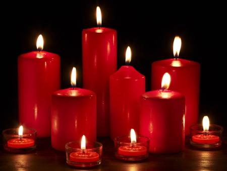 luz de velas: Grupo de quemar velas sobre fondo negro. Foto de archivo