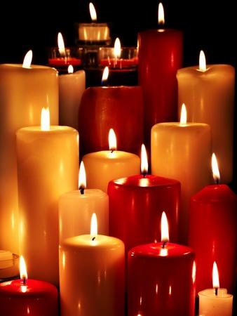 lit: Group of burning candles on  black background.