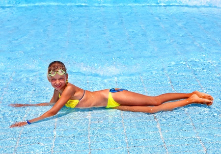 Child in swimming pool. Water sport. photo