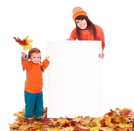 Happy family with child on autumn leaves holding banner. photo