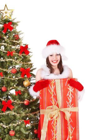 Girl in santa hat holding gift box by christmas tree.  Isolated. Stock Photo - 10971561