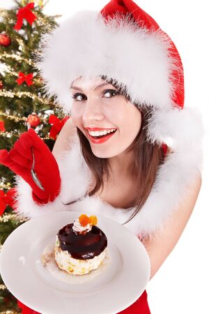 woman eating cake: Christmas girl in red santa hat and cake on plate. Isolated. Stock Photo