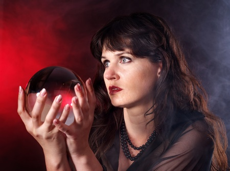 foretell: Young woman  with crystal ball. Beauty and fashion.