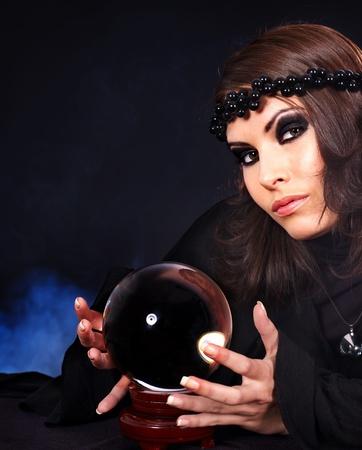 Mujer joven con la bola de cristal. Adivinación.