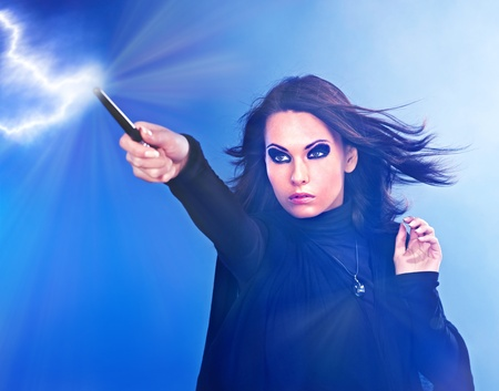 girl magic wand: Young woman with magic wand casting spells. Stock Photo