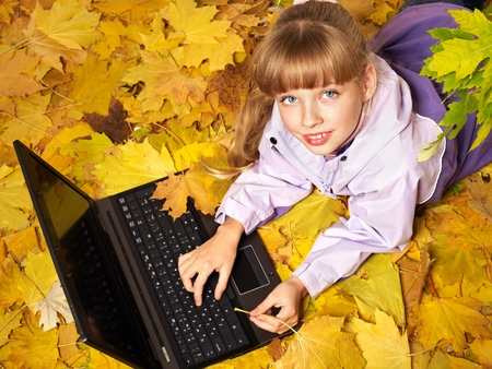 Childl in autumn leaves with laptop. Outdoors. photo