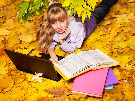 Child in autumn leaves with laptop and books. Outdoors. photo
