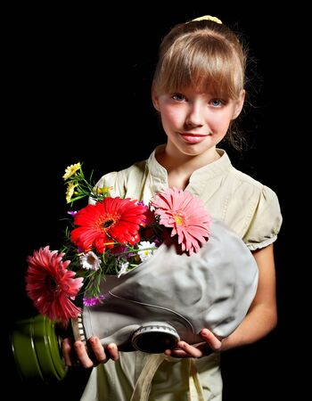 Little girl holding flowers and gas mask . photo