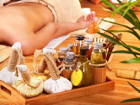 body oil: Young woman getting massage in bamboo spa.