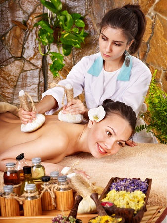 Woman getting thai herbal compress massage in spa. Stock Photo - 11174725