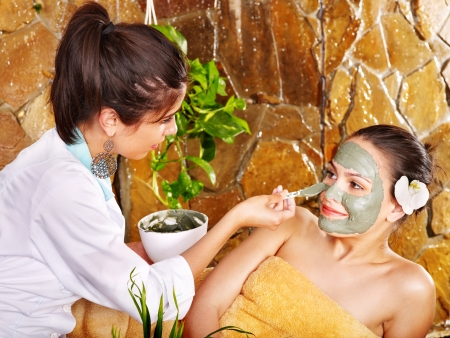 Beautiful girl having clay body mask apply by beautician. photo
