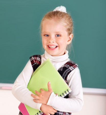 Happy schoolchild near blackboard. photo