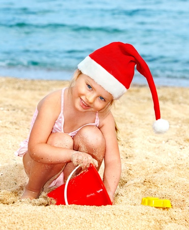 beach happy new year: Child in santa hat playing on  beach. Summer New Year.