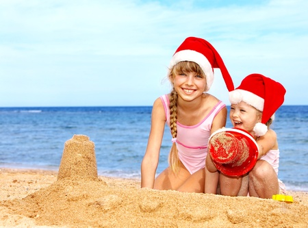 Children in santa hat playing on  beach. Summer New Year.