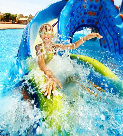 Child on water slide at aquapark. Summer holiday. Stock Photo - 11209877