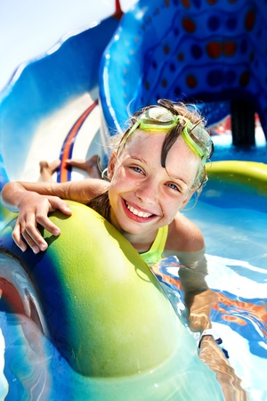 summer wear: Child on water slide at aquapark. Summer holiday.