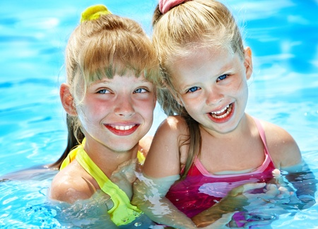 Children in swimming pool. Summer outdoor. photo
