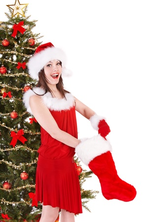 Girl in santa hat holding christmas stocking and gift box by christmas tree.  Isolated. photo