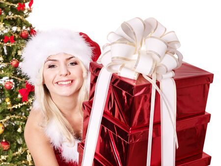 Girl in santa hat holding stack gift box near christmas tree.  Isolated. Stock Photo - 11174851