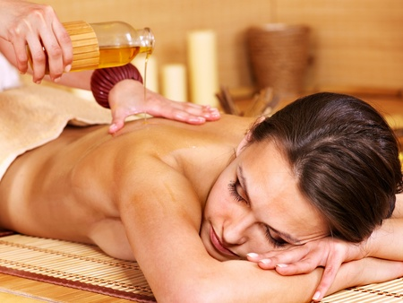massage oil: Young woman getting massage in bamboo spa.