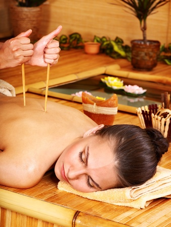 Young woman getting bamboo massage. photo