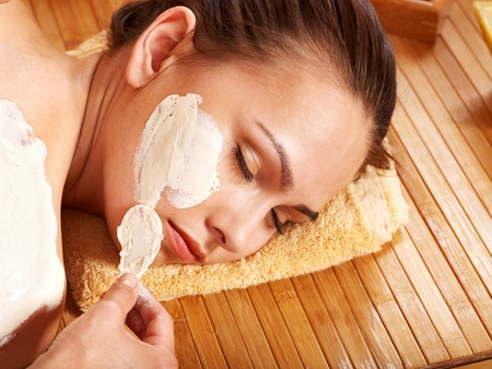 Beautiful girl having clay body mask apply by beautician. Stock Photo - 11174907