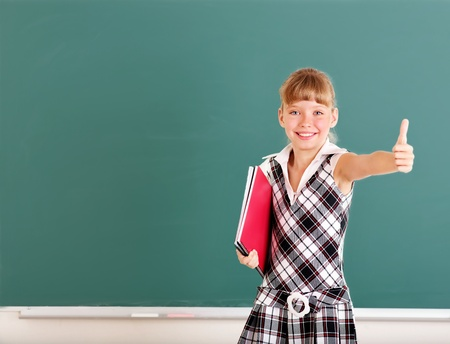schoolroom: Happy schoolchild near blackboard.