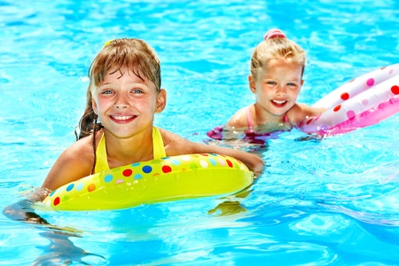 Children sitting on inflatable ring in swimming pool. photo