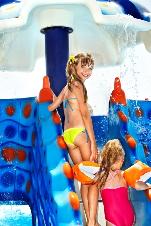 armbands: Children on water slide at aquapark. Summer holiday. Stock Photo