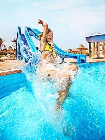 Niño en tobogán en el parque acuático. Vacaciones de verano.