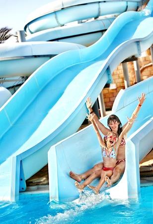 Niño con la madre en el tobogán de agua en el parque acuático. Vacaciones de verano. Foto de archivo