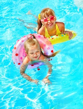 meisje zwemmen: Kinderen zitten op opblaasbare ring in het zwembad.