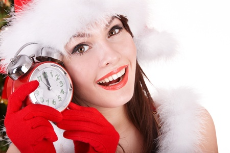 Christmas girl in santa hat holding clock.  Isolated. Stock Photo - 11210014