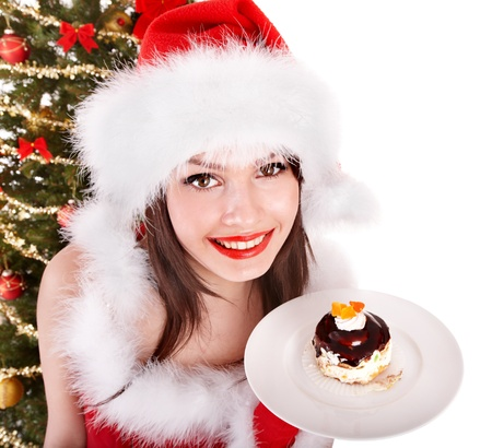 Girl in santa hat eat cake on plate by christmas tree.. Isolated. photo