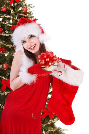 Girl in santa hat holding christmas socks and gift box near christmas tree.  Isolated. photo